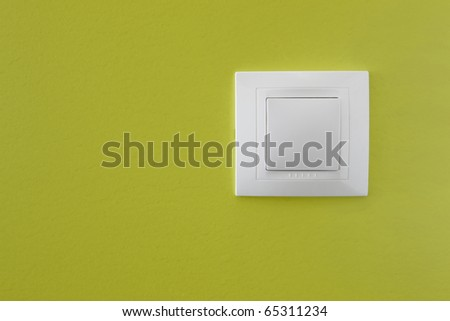 Simple light switch on a green wall - stock photo