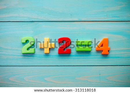 Simple mathematical addition on a wooden surface - stock photo