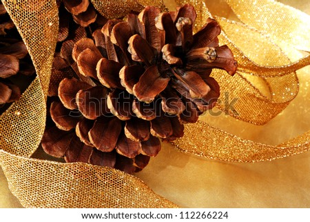 Simple natural holiday decor with pine cones and sparkly gold mesh ribbon on gold metallic paper.  Macro with shallow dof. - stock photo