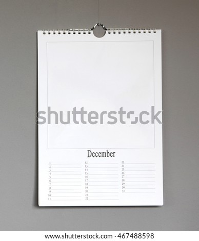 Simple old birthday calendar hanging on a grey wall, copy space - December
