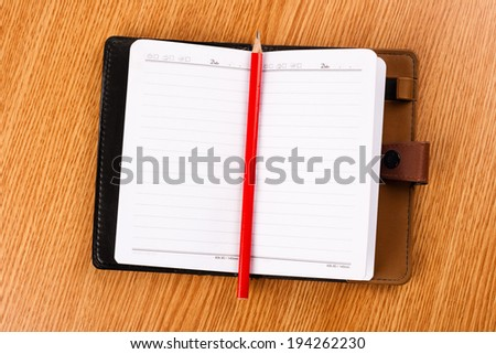 Simple opened business agenda with red pencil - stock photo