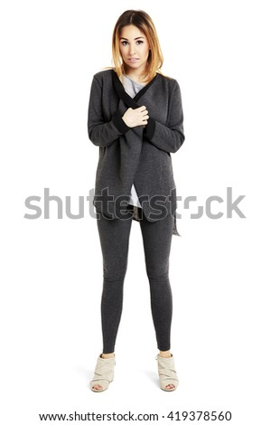Simple picture of beautiful girl. She is hiding something under her blouse. - stock photo