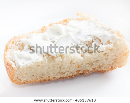 Simple piece of bread with cottage cheese spreaded on white isolated background