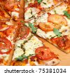 Simple pizza with mozzarella cheese, tomatoes and pesto. - stock photo