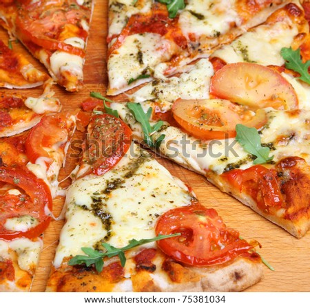 Simple pizza with mozzarella cheese, tomatoes and pesto. - stock photo