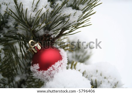 Simple red Christmas ornament in the snow - stock photo