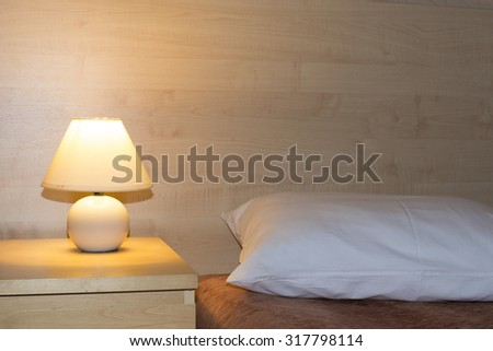 simple room interior with illuminated bed light on wooden table and focus on pillow