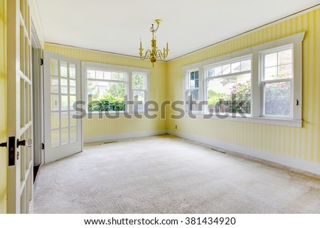 simple room with carpet, and yellow striped walls.