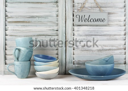 Simple rustic blue crockery against shabby wooden shutters: dish, bowls, mugs and Welcome plate.