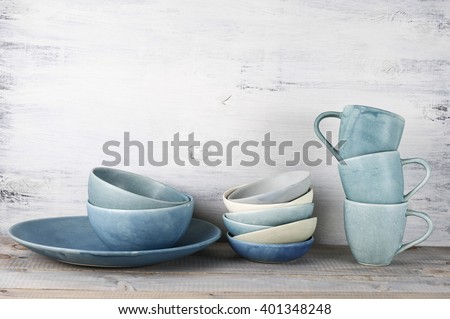 Simple rustic blue crockery against wooden wall: dish, stack of bowls and mugs. - stock photo