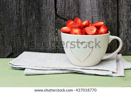 Simple rustic composition with bowl full of sweet tasty ripe strawberry, fresh natural dessert. Vintage kitchen decor. Romantic style. Red, grey and green color - stock photo
