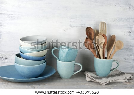 Simple rustic handmade blue crockery against white wooden wall: dish, stack of bowls. mugs and wooden cooking utensils set. - stock photo