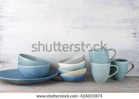 Simple rustic handmade blue crockery against wooden wall: dish, stack of bowls and mugs.