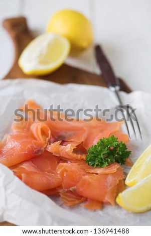 Simple shot of organic smoked salmon & lemon with parsley garnish displayed on a board - shallow dof - stock photo