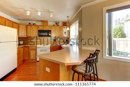 Simple standard American wood  kitchen with hardwood floor and chairs.