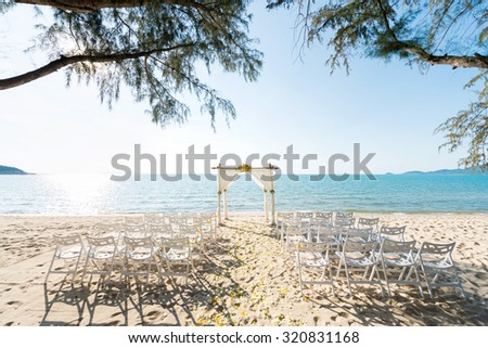 simple style wedding arch and decoration, venue, setup on tropical beach, outdoor beach wedding. - stock photo