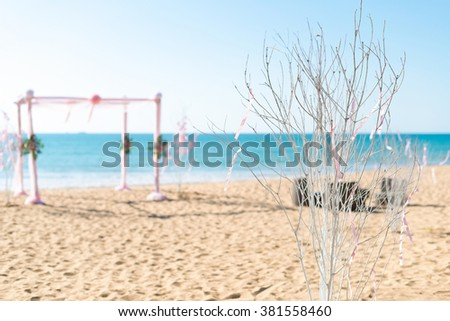 simple style wedding arch and decoration, venue, setup on tropical beach, outdoor beach wedding. focusing on twigs branch shallow depth of field. - stock photo