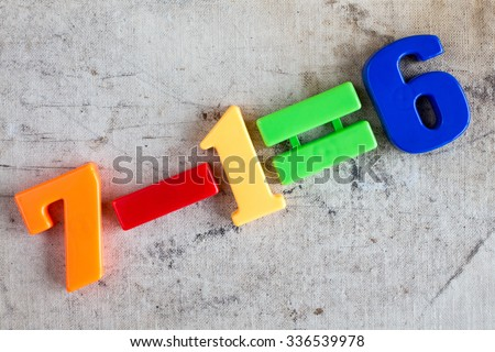 Simple subtraction formula with colorful plastic numbers - stock photo