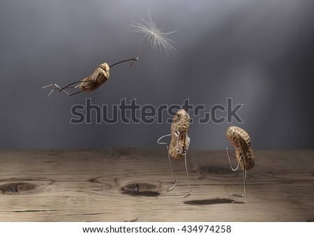 Simple Things - Peanut Man Flying with Dandelion Blowball Umbrella - stock photo