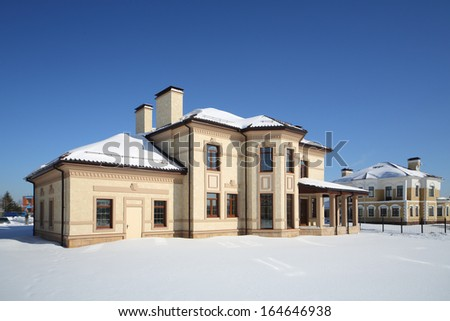 Simple two-storey new cottage with many windows on sunny frosty winter day. - stock photo