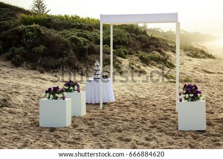Simple wedding arch decor on beach stock photo royalty free simple wedding arch and decor on beach sand with purple flowers beach wedding sunset junglespirit Image collections