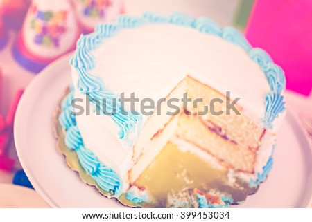 Simple white Birthday cake slice with white and blue icing.