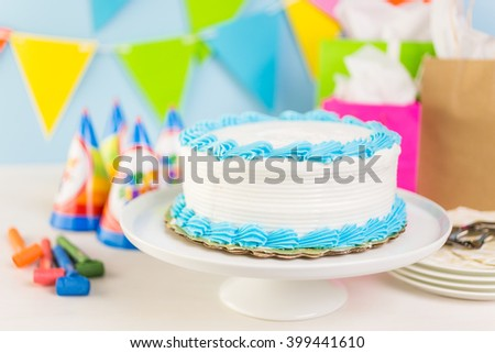 Simple white Birthday cake with white and blue icing.