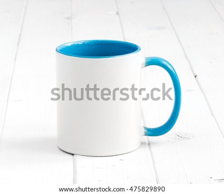 simple white cup with blue inside and handle on a planked table