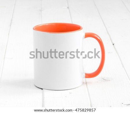 simple white cup with orange inside and handle on a planked table