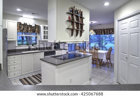 Simple white dated kitchen with island - stock photo