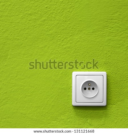 simple white electric socket on green wall - stock photo