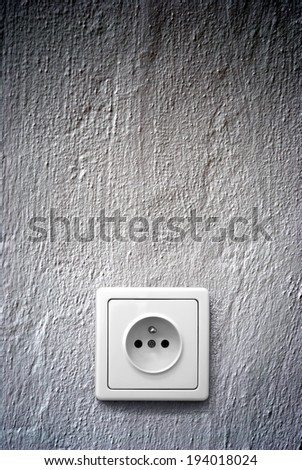 simple white electric socket on grey wall - stock photo