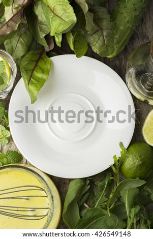 Simple white plate on a wooden background surrounded by chard leaf, sauce, slices of lime, fresh cucumbers, arugula for the preparation of fresh light summer salad. The concept of pure healthy foods. - stock photo