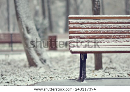 Simple wooden bench in snowy white landscape - stock photo