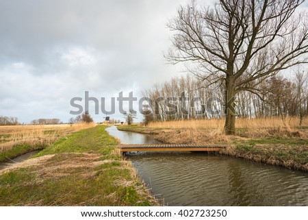 Simple wooden bridge made of planks bridges a small creek in a Dutch nature reserve on an overcast day at the beginning of spring. In the background an old windmill is visible. - stock photo