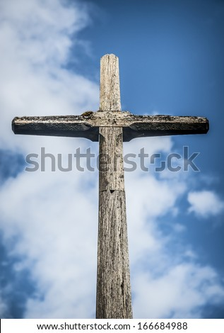 Simple wooden Christian cross against a blue sky. - stock photo