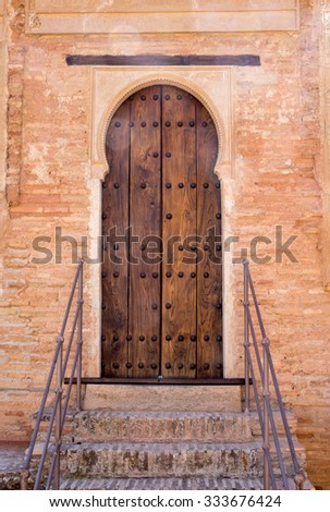 Simple wooden doorway with ornate arch in gardens of Alhambra palace Granada, Spain - stock photo