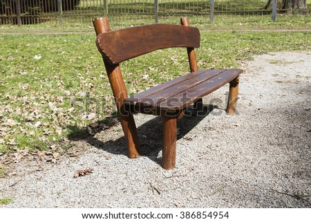simple wooden garden bench in the park - stock photo