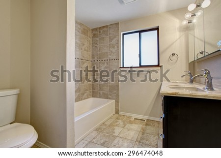 Simple yet elegant bathroom with nice bathtub and tile floor. - stock photo