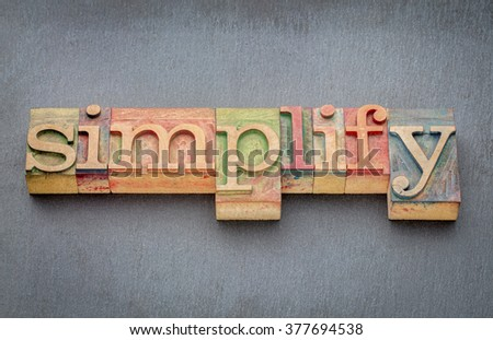 simplify word in letterpress wood type printing blocks stained by color inks against slate stone - stock photo