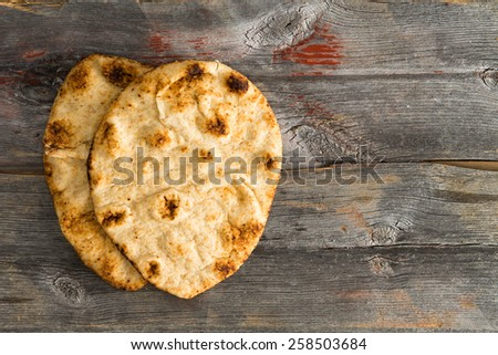 Simply delicious baked crusty whole grain naan flatbreads, a leavened bread cooked in a tandoor clay oven, served on authentic old wooden Picnic Table shot from above with copyspace on the right - stock photo