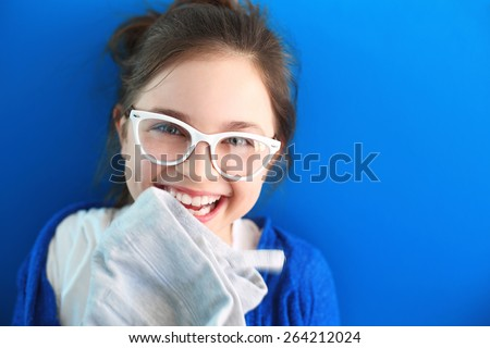 Sincere smile, happy child.Beautiful smiling girl in white glasses on blue background - stock photo