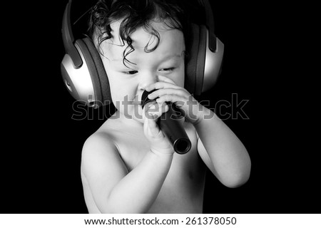 Sing baby with headphone and microphones, on a black background. - stock photo