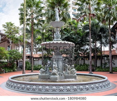 SINGAPORE- April 6: An ornate cast-iron fountain at the courtyard of Singapore's famous Raffles Hotel April 6, 2011. The antique fountain was made in Glasgow and brought to Singapore in the 1890s. - stock photo