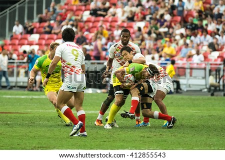 SINGAPORE-APRIL 16: Australia 7s Team (yellow/green) plays against Japan 7s team (red/white) during Day 1 of HSBC World Rugby Singapore Sevens on April 16, 2016 at National Stadium in Singapore