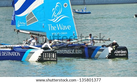 SINGAPORE - APRIL 13: Crew of The Wave, Muscat, steering the boat at the Extreme Sailing Series race at Marina Bay Reservoir April 13, 2013 in Singapore