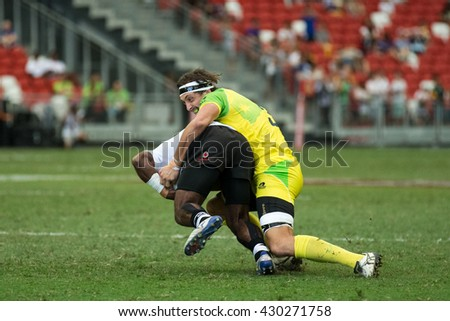 SINGAPORE-APRIL 17:Fiji 7s Team (white) plays against Australia 7s team (yellow/green) during Day 2 of HSBC World Rugby Singapore Sevens on April 17, 2016 at National Stadium in Singapore