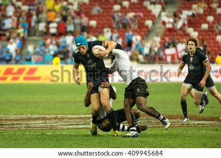 SINGAPORE-APRIL 16:Fiji 7s Team (white) plays against England 7s team (navy blue) during Day 1 of HSBC World Rugby Singapore Sevens on April 16, 2016 at National Stadium in Singapore