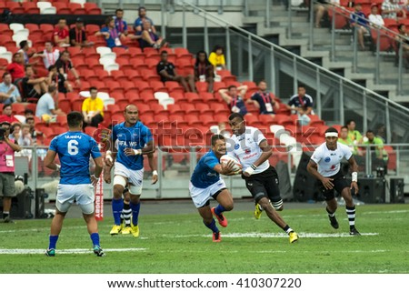 SINGAPORE-APRIL 16: Fiji 7s Team (white) plays against Samoa 7s team (blue) during Day 1 of HSBC World Rugby Singapore Sevens on April 16, 2016 at National Stadium in Singapore
