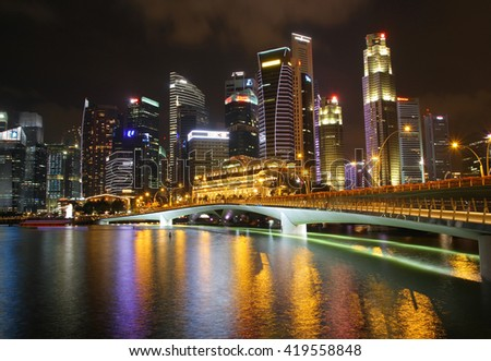 SINGAPORE - APRIL 10,2016: Financial district skyscrapers and the Jubilee Bridge at Merlion Park. A newly created pedestrian bridge at Marina Bay  - stock photo
